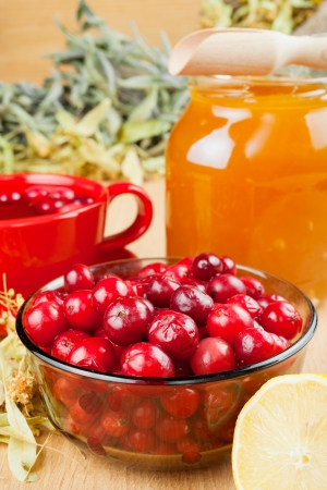cranberries, jar with honey, fruit tea cup, healing herbs and lemon photo
