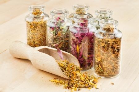 homeopatia: hierbas curativas en botellas de vidrio y cuchara de madera, hierbas medicinales Foto de archivo