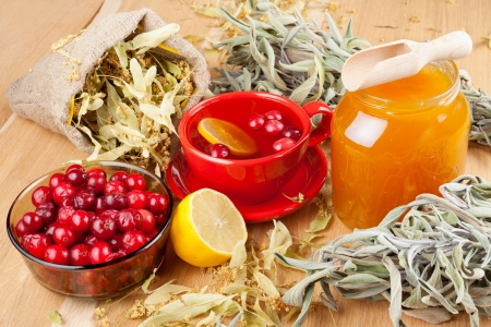 cranberries, jar with honey, fruit tea cup, healing herbs and lemon Stock Photo - 16577754