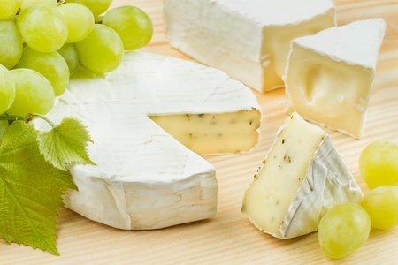 camembert: gourmet cheese and grapes on wooden board