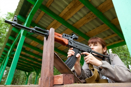 airsoft gun: Young woman aiming at a target and shooting an automatic rifle for strikeball  Focus on the rifle  Stock Photo