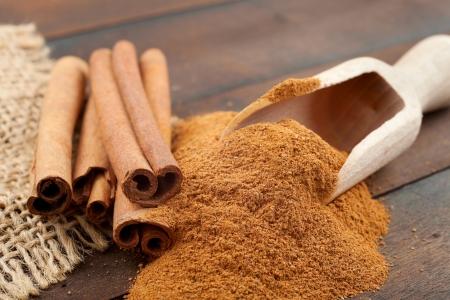 Cinnamon sticks and cinnamon powder in wooden scoop