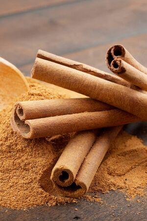 cinnamon bark: Cinnamon sticks and cinnamon powder in wooden scoop