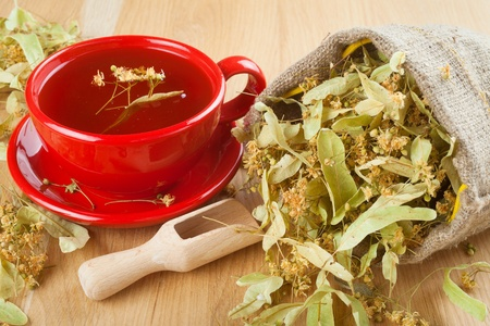 linden tea: cup of linden tea and flowers in canvas bag on wooden table Stock Photo