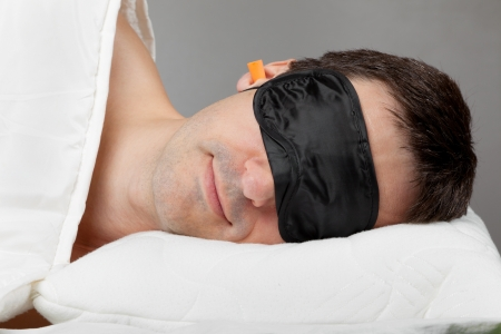 blindfold: Man with Sleeping mask and earplugs lying in bed