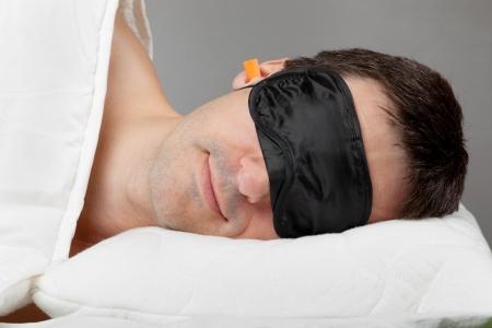 sleeplessness: Uomo con la maschera Dormire e tappi per le orecchie a letto