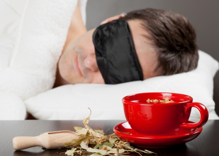 resting mask: Man with Sleeping mask sleep on a bed, cup of herbal tea in the foreground  Focus on tea cup Stock Photo