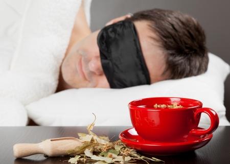 Mann mit Schlafbrille schlafen auf einem Bett, Tasse Kräutertee im Vordergrund Fokus Tasse Tee Standard-Bild