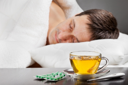 sleeping tablets: sick man lying in bed with fever,  cup of herbal tea, pills and thermometer in the foreground