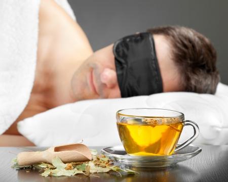 sleeplessness: Uomo con la maschera di sonno Dormire su un letto, tazza di t� alle erbe in primo piano