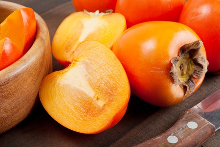 persimmons: persimmons on wooden table