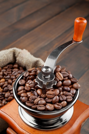 coffee grinder with coffee beans on wooden table photo