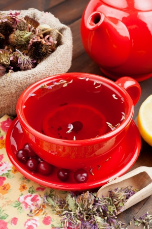 red tea cup and teapot, healing herbs and lemon on kitchen table photo