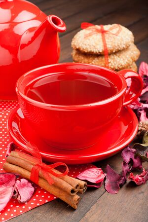 holiday tea in red cup, cookies, teapot and cinnamon sticks on kitchen table photo