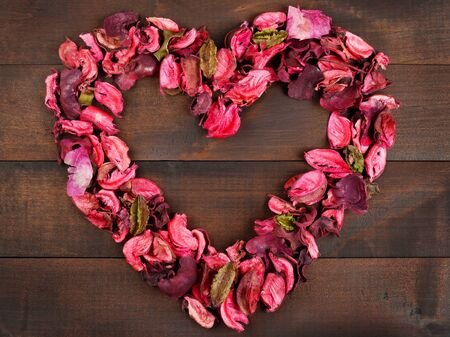 Flower Petals forming a heart shape against wooden background photo