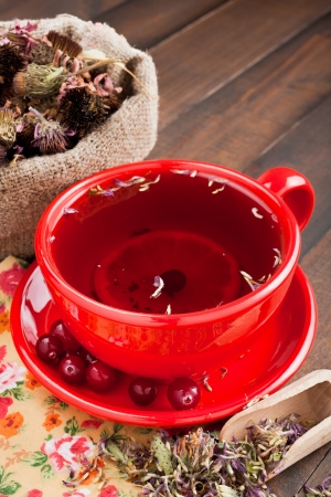 red tea cup, healing herbs on kitchen table photo