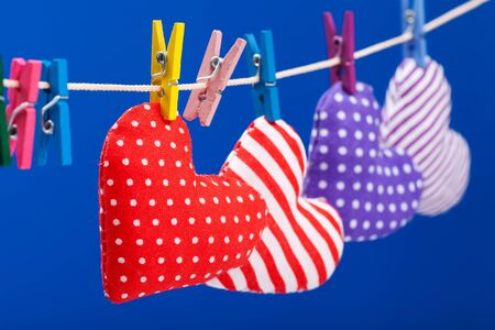 hearts hanging on a clothesline with clothespins, focus on red  Blue background photo