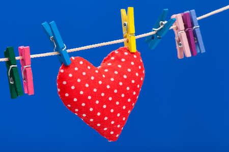 pin stripe: red heart hanging on a clothesline with clothespins, blue background