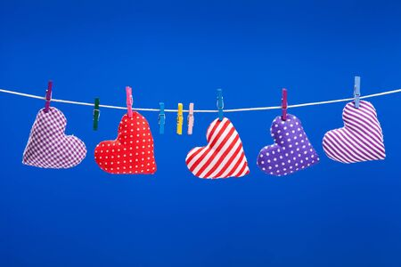hearts hanging on a clothesline with clothespins, blue background photo