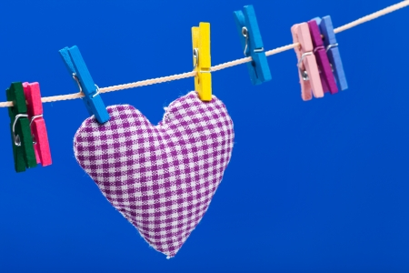 single heart on clothesline with clothespins, blue background photo