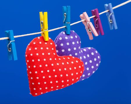 two hearts: two hearts hanging on a clothesline with clothespins, focus on red  Blue background Stock Photo