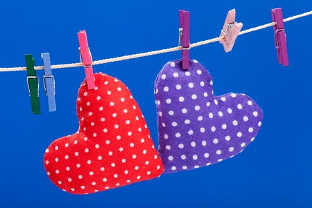 two hearts hanging on a clothesline with clothespins, blue background photo