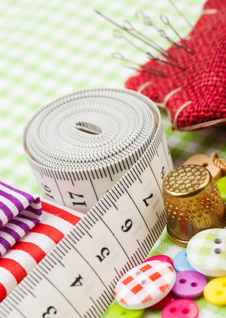 made to measure: Sewing items: buttons, colorful fabrics, measuring tape, pin cushion, thimble