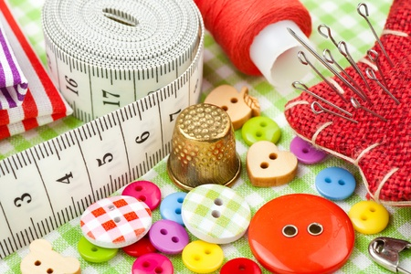 made to measure: Sewing items: buttons, colorful fabrics, measuring tape, pin cushion, thimble, spool of thread   Stock Photo