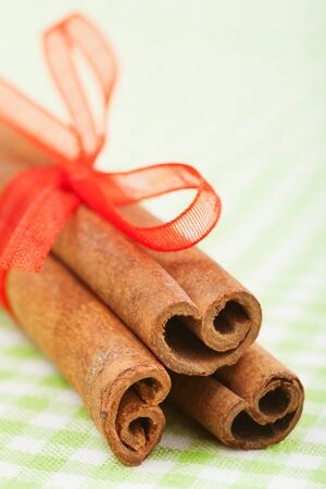 cinnamon sticks with red ribbon on green tablecloth photo