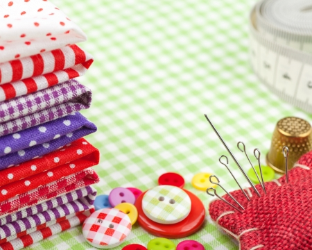 Sewing items  buttons, colorful fabrics, measuring tape, pin cushion, thimble