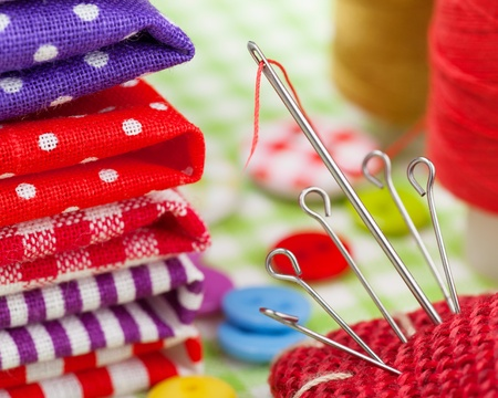 art and craft equipment: Sewing items  colorful fabrics, buttons, pin cushion, thimble, spool of thread