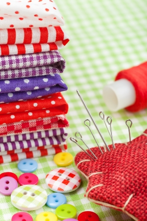 Sewing items  colorful fabrics, buttons, pin cushion, thimble, spool of thread  photo