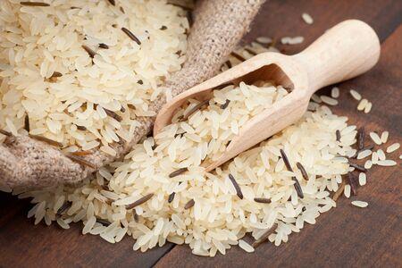 wooden scoop: rice in burlap sack with wooden scoop