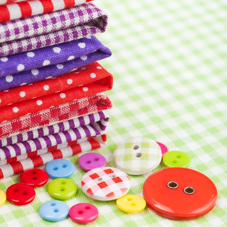 Sewing items: buttons, colorful fabrics, measuring tape, pin cushion, thimble photo