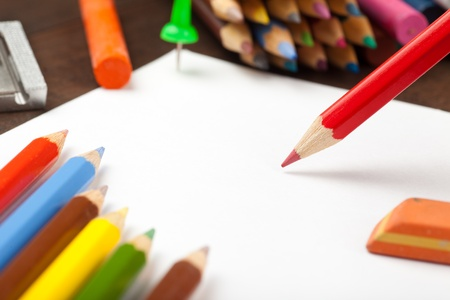 Red pencil draws on white paper sheet  Colored pencils, crayons, eraser on table  Stock Photo - 17707276