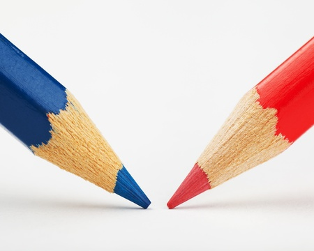 opposition: red and blue pencils against each other on a white paper sheet Stock Photo