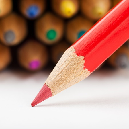 red pencil draws or writing on white paper sheet, colored pencils as background Stock Photo - 17707278