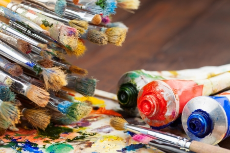 art brushes, oil paint tubes, artist palette on wooden table Stock Photo - 17707290