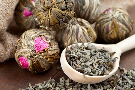 Green tea balls with flowers and wooden spoon with tea on kitchen table Stock Photo - 17859912