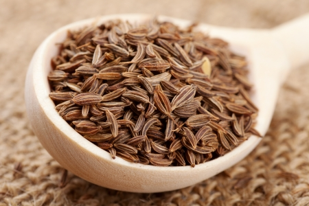 fennel seeds: cumin seeds in wooden spoon