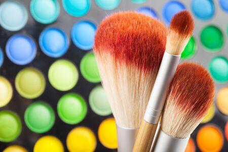 pinceles de maquillaje y un conjunto de sombras de ojos de colores como fondo