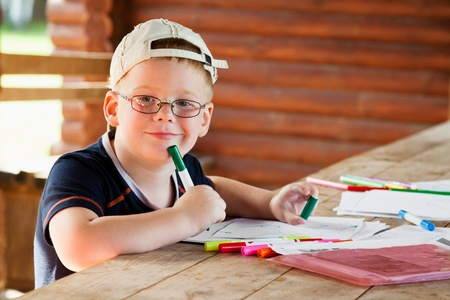 cute boy drawing in wooden gazebo outdoors Stock Photo - 19156002