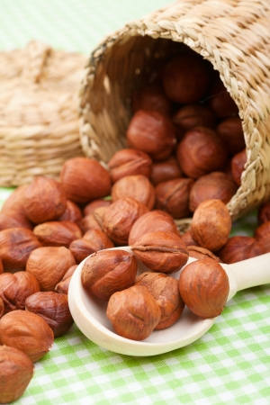 willow fruit basket: hazelnuts, wooden spoon and basket on kitchen table Stock Photo