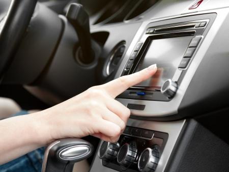 vinger op het dashboard met gps-paneel en tv dvd audiosysteem