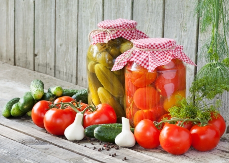 canned tomatoes and pickled cucumbers, homemade preserved vegetables photo