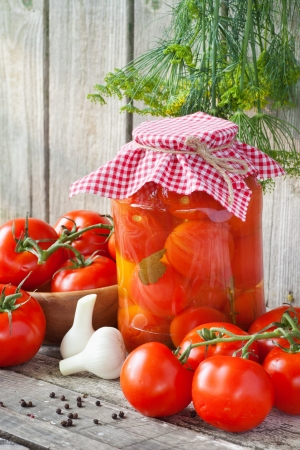sterilized: Homemade tomatoes preserves in glass jar. Fresh and canned tomatoes on wooden board Stock Photo