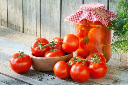 sterilized: Homemade tomatoes in glass jar. Fresh and canned tomatoes on wooden board Stock Photo