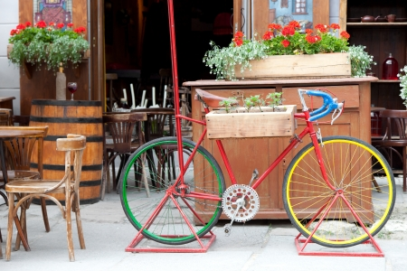 Old colorful bicycle carrying flowers, street cafe in Lvov city Stock Photo - 21427671