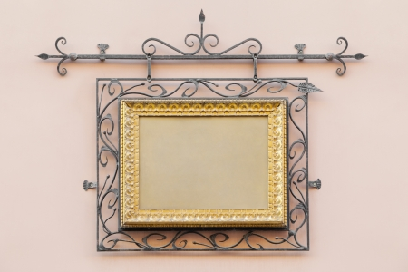 vintage frame decorated with wrought iron on the home wall of  house outdoors photo
