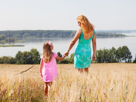 Mother and daughter walking  in summer field near lake on a sunny day photo